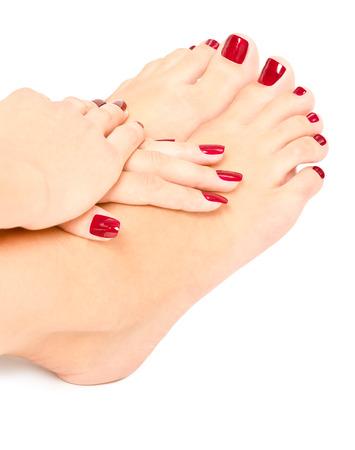 手入れが行き届いている女性の足、白い背景で隔離の赤のマニキュアの手