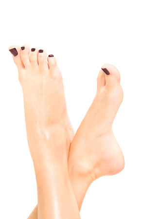 Beautiful female feet with brown pedicure isolated on white background Stock Photo