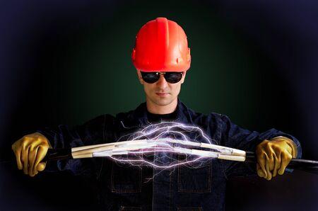 Elektriciens in isolerende handschoenen houdt kabels die bliksem schieten