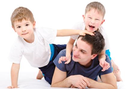 Cheerful father and sons lying isolated on white background