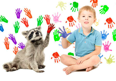 Cute boy with raccoon sitting on the background of handprints Stock Photo