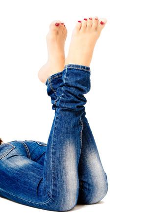 pies sexis: cuidadas piernas femeninas en los pantalones vaqueros aislados en el fondo blanco