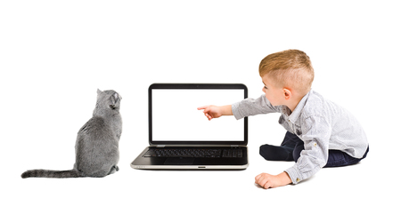 Kid points finger at the screen of laptop sitting with a cat isolated on a white background
