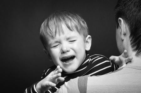 Retrato de un hijo llorando en manos de un padre