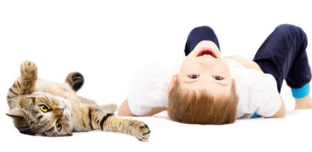 白い背景の快活な少年と猫の肖像画スコットランドまっすぐその背中の上に横たわる分離