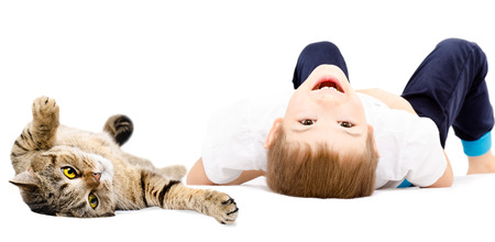 scottish straight: Portrait of a cheerful boy and cat Scottish Straight lying on its back isolated on white background