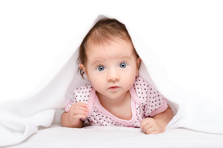 Portrait of a cute baby, lying under towel, isolated on white background Stock Photo