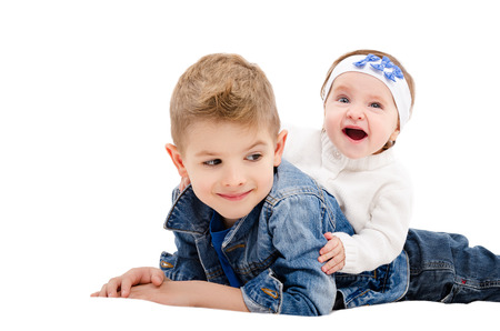 The brother and his cheerful little sister lying isolated on white background Stock Photo