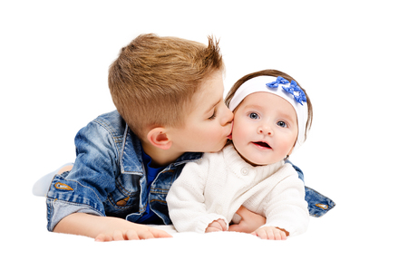 Portrait of brother kissing his little cute sister lying isolated on white background
