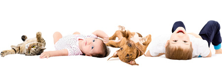 Group of children and pets, laying on a back, isolated on white background