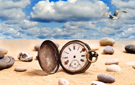 Old pocket watch on the sand on a background a cloudy sky