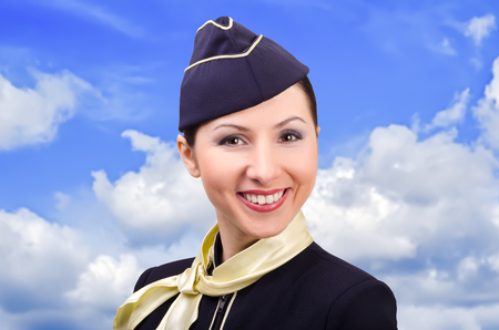 Portrait of beautiful smiling stewardess on a background a cloudy sky