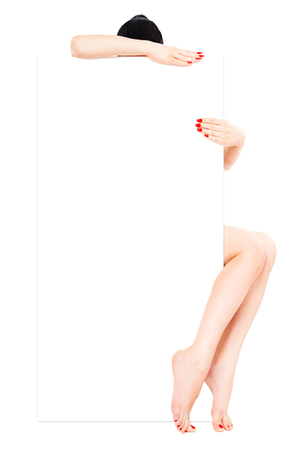 Beautiful well-groomed woman with red manicure, sitting behind a banner, isolated on white background