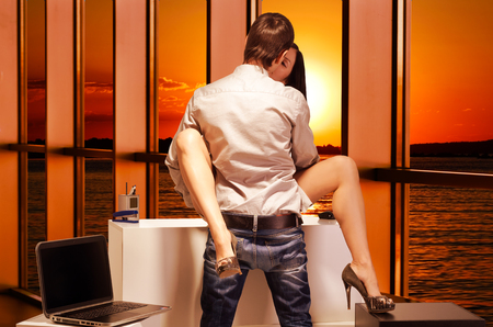 Beautiful young couple having sex in the office at sunset Stock Photo - 78996936