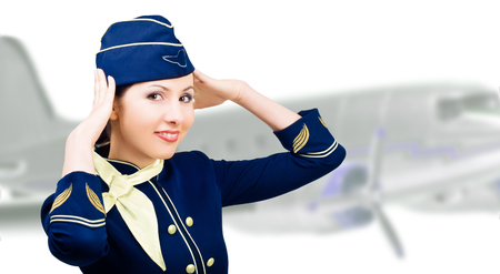 Portrait of smiling beautiful stewardess on a background the airplane photo