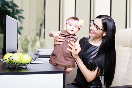 Beautiful young mother with her little cute daughter in the office photo