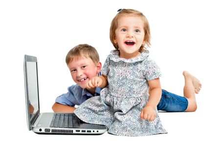 Cheerful children, sitting in front of a laptop, isolated on white background