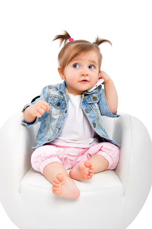 Portrait of a beautiful baby girl, talking on the phone, isolated on white background