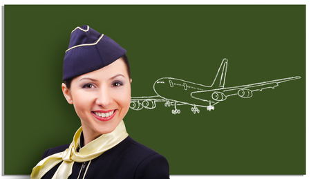 Portrait of a beautiful cheerful stewardess on the background of a board with a drawn airplane