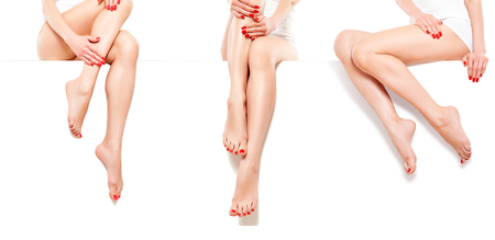 Three beautiful slim woman with red manicure, sitting at banner, isolated on white background