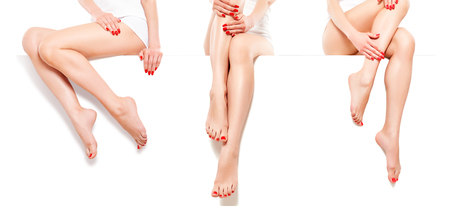 Three beautiful slim women with red manicure, sitting at banner, isolated on white background Stock Photo