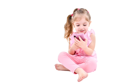 Cute little girl sitting with mobile phone isolated on white background