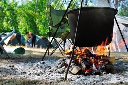 Cooking in a cauldron on a camping background