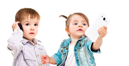 Cute little kids with mobile phones isolated on white background. The concept of the modern generation of children.