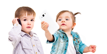 The concept of the modern generation of children. Cute little kids with mobile phones. Stock Photo