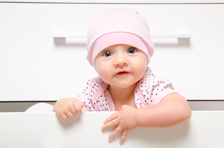 Portrait of a cute happy baby sitting in a drawer chest Banco de Imagens - 121502478