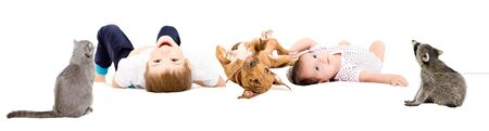 Group of cute happy children and pets lying isolated on white