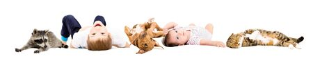 Group of cute children and pets lying isolated on white