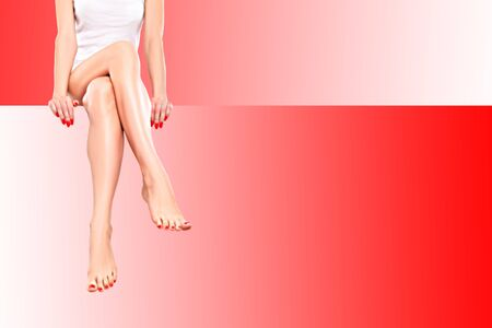 Beautiful slim sexy woman with red manicure sitting at banner on red background