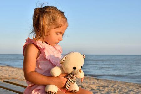 Sad little girl with a toy bear sitting on the beach Stok Fotoğraf