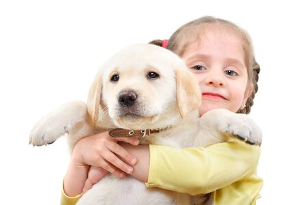Portrait of a cute girl holding a Labrador puppy in her arms isolated on white background