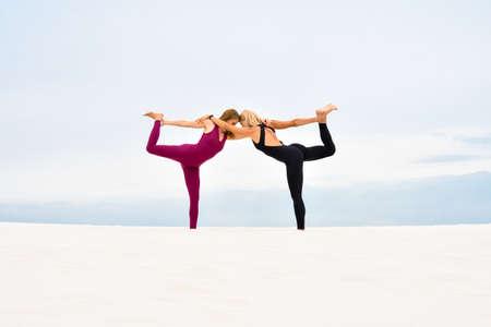 Two beautiful young women performing together yoga pose nataradzhasana Stock fotó - 155445206