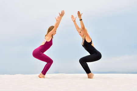 Two beautiful young women doing yoga pose Utkatasana together Stock fotó - 155445208