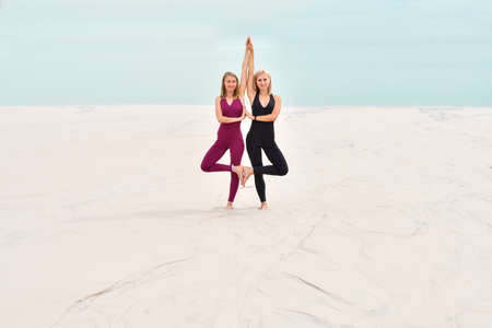 Two beautiful slender young women standing together in sports overalls on the beach Stock Photo