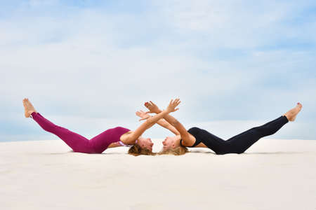 Two beautiful young women doing steamy yoga on the beach
