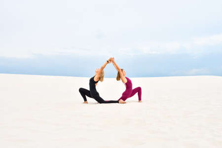Two beautiful young women performing yoga together on the sand