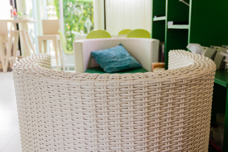 arm chairs: white rattan armchair in the living room.