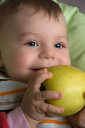 first teeth: Baby with the first teeth, eating apple.