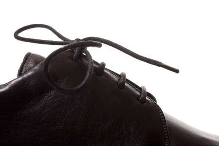Fragment of classic black shoe with laces. Isolated on white background