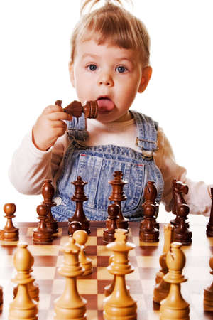 girl behind chess desk holding a chess piece in her hand and trying to taste it. Isolated on white background.