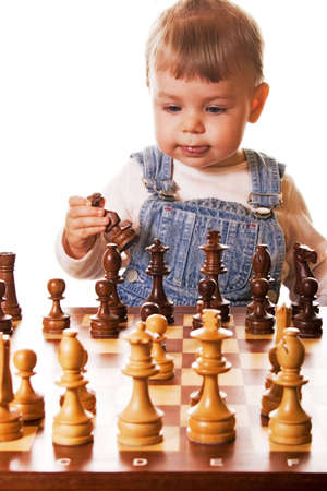 girl behind chess desk holding a chess piece in her hand. Isolated on white background.