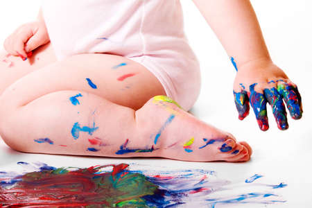manos sucias: Baby's pierna y los dedos manchados de colores. Aislado en fondo blanco.