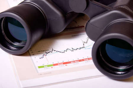emerging: Binoculars and table with financial figures.