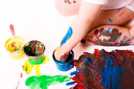 Child painting with his hands using several color cans. White background.