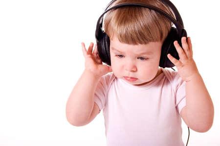 Little girl listening to music in the headphones. Studio shot, isolated on white background.