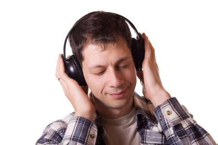 Young mean in headphones with closed eyes listening to the music. Studio shot, isolated on white background. Stock Photo